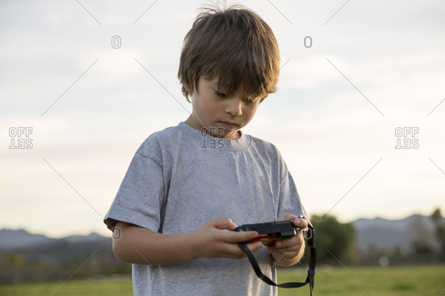 Boy looking at digital camera in park