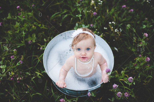 Overhead view of baby girl bathing in a tin bathtub in a wild flower meadow