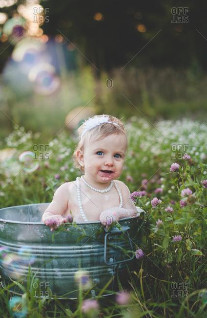Portrait of baby girl bathing in a tin bathtub in a wild flower meadow