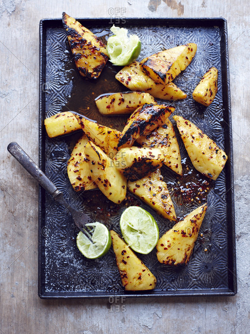 Tray of grilled pineapple with lime