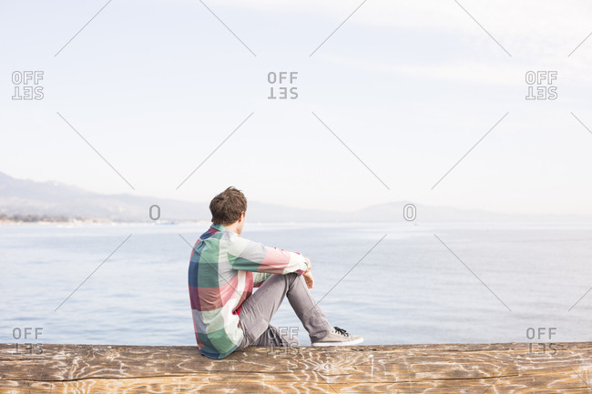Young man looking at view across the water