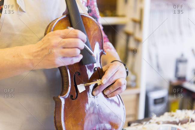 Violin maker making violins in production studio