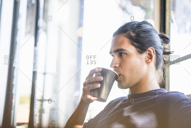 Young man drinking coffee, indoors