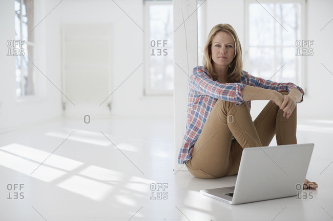 Portrait of mature woman using laptop in empty office space