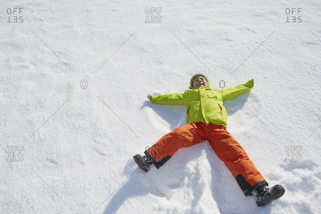 Young boy making snow angel in snow