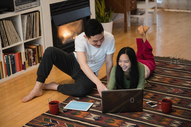 Happy couple using laptop near fireplace in living room at home