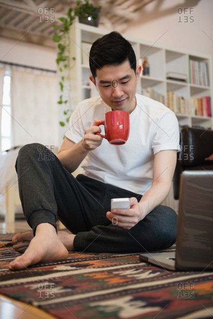 Man using mobile phone while having coffee in living room at home