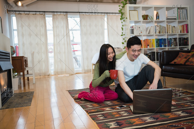 Happy couple using laptop while having coffee in living room at home