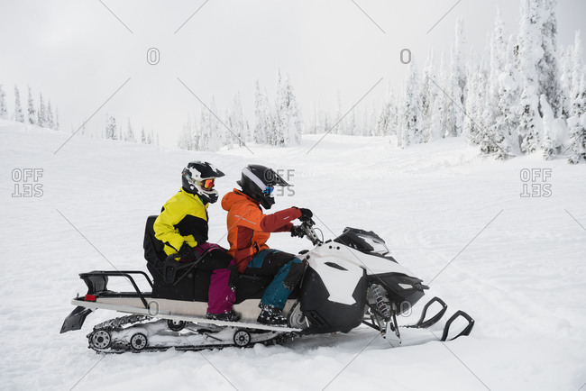 Couple riding snowmobile in snowy alps during winter