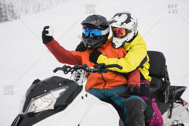 Couple taking selfie on mobile phone while riding snowmobile during winter