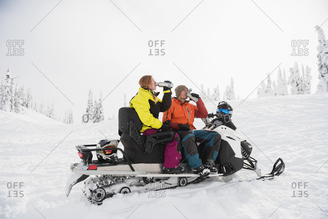 Couple having coffee from thermos while relaxing on snowmobile during winter