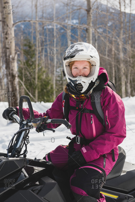 Woman relaxing on snowmobile during winter