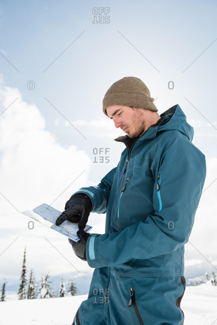 Man pointing at map in snowy alps during winter