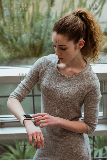 Young female executive using smart watch in office