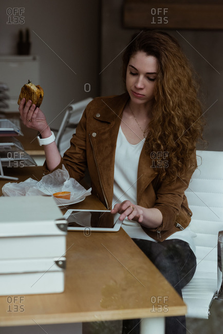 Female executive using digital tablet while having breakfast in office