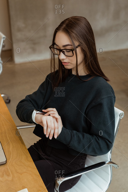 Female executive using smart watch at desk in office