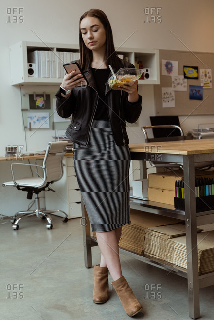 Female executive using mobile phone while having meal in office