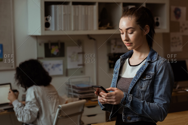 Young female executive using mobile phone in office
