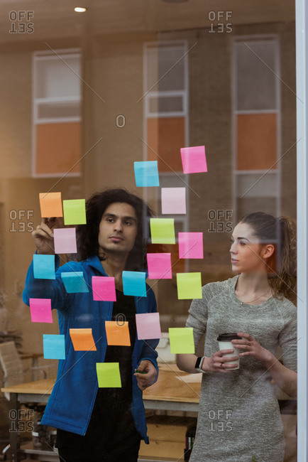 Business colleagues discussing over sticky notes in office