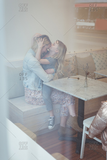 Daughter kissing mother on forehead in the restaurant
