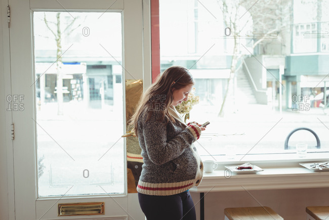 Pregnant woman using mobile phone in the restaurant