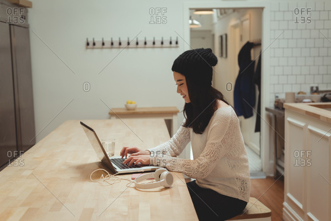 Beautiful woman using laptop in kitchen at home
