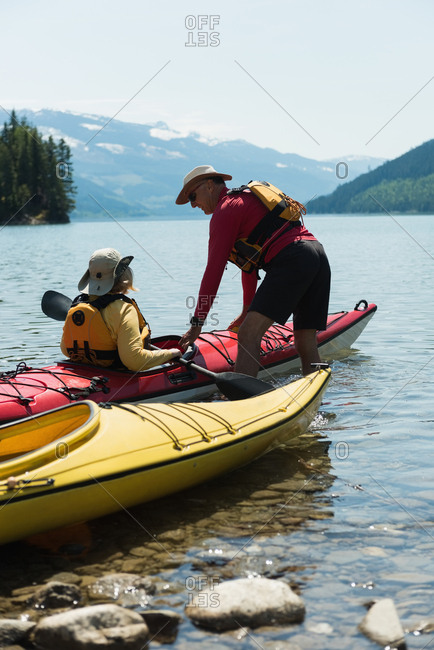 Mature man assisting woman for kayaking in lake against mountain