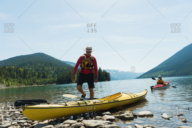 Man walking towards kayak with woman kayaking in background against sky