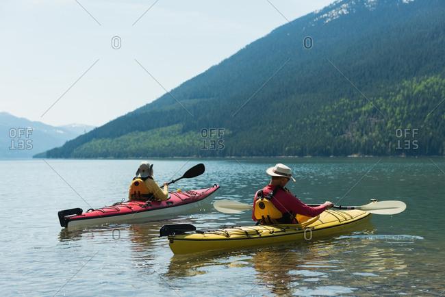 Couple kayaking in lake against mountain