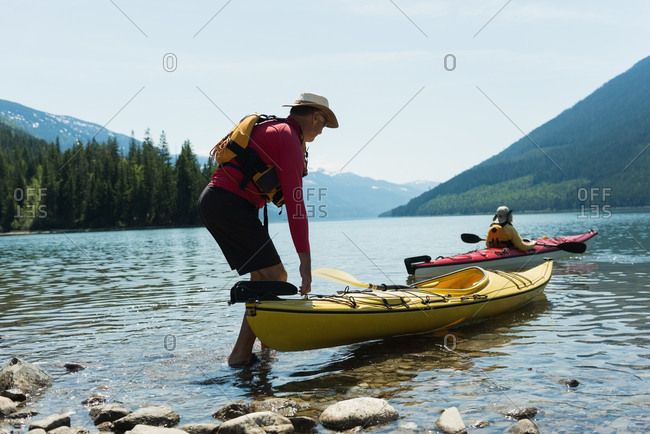 Man holding kayak while woman kayaking in lake against sky during sunny day