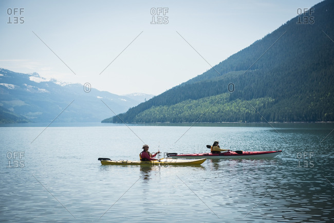 Side view of couple kayaking in lake by mountain against sky