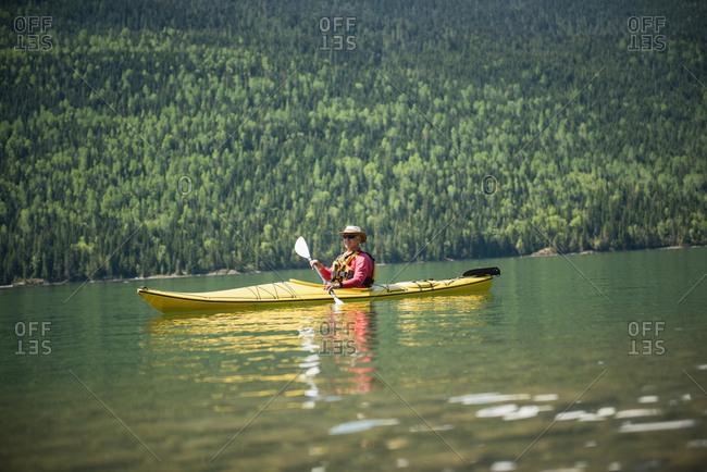 Man kayaking in lake by mountain