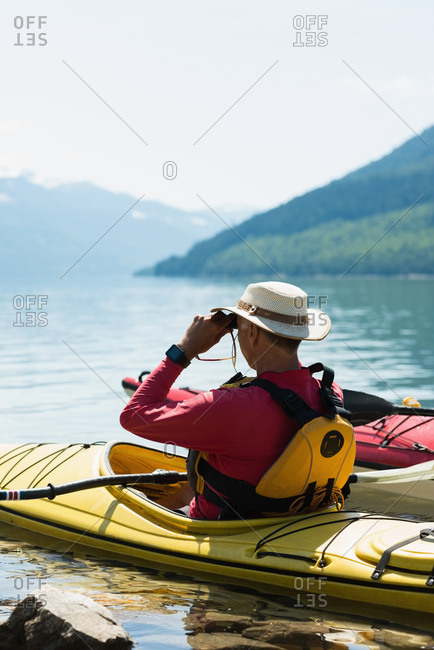 Man using binoculars while sitting in kayak over lake against sky