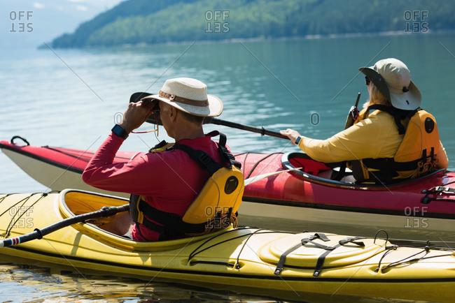 Man using binoculars while kayaking with woman in lake during sunny day