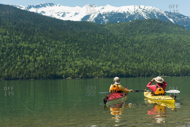 Rear view of couple kayaking in lake by mountain