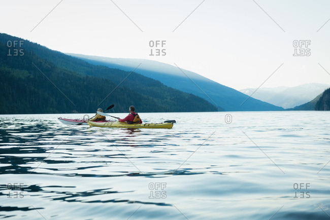 Mature couple kayaking in lake by mountain against clear sky
