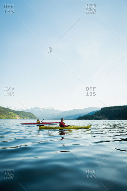 Water surface lever of couple kayaking in lake against blue sky