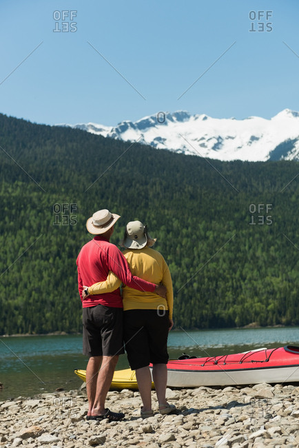 Rear view of mature couple standing at lakeshore against mountains