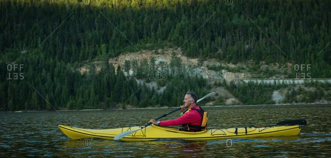 Side view of mature man oaring while kayaking in lake