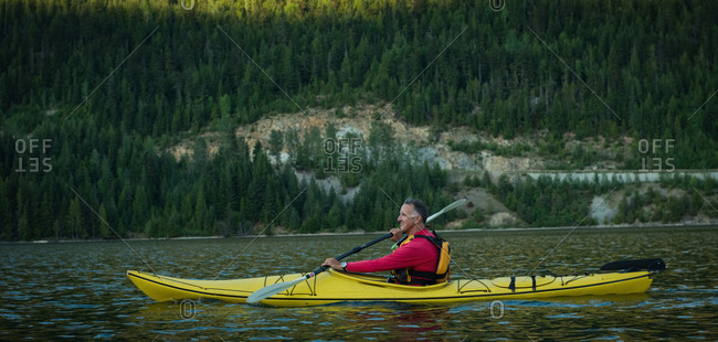 Side view of mature man oaring while kayaking in lake
