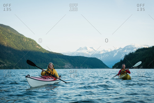 Couple in kayak over lake against blue sky