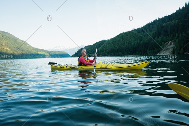 Side view of man kayaking in lake by mountain against sky