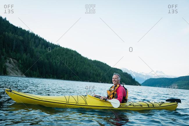 Smiling man kayaking in lake by mountain against sky