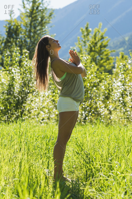 Beautiful woman doing yoga in a green forest on a sunny day