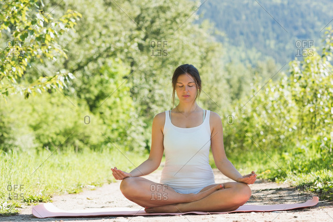 Woman doing meditation pose on yoga mat in forest