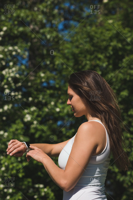 Woman using smart watch in park on a sunny day