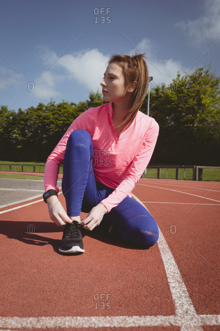 Young woman in sports clothing looking away on running track