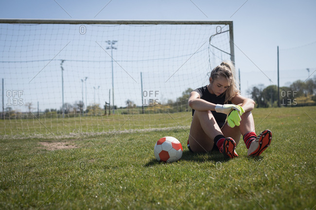 Full length of tired female soccer player relaxing on playing field