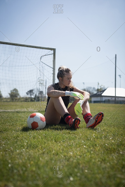 Full length of female soccer player relaxing on playing field