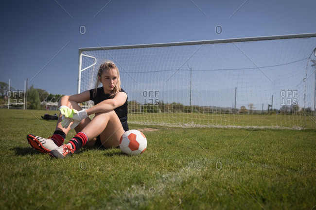 Full length of female soccer player relaxing by goal post on playing field